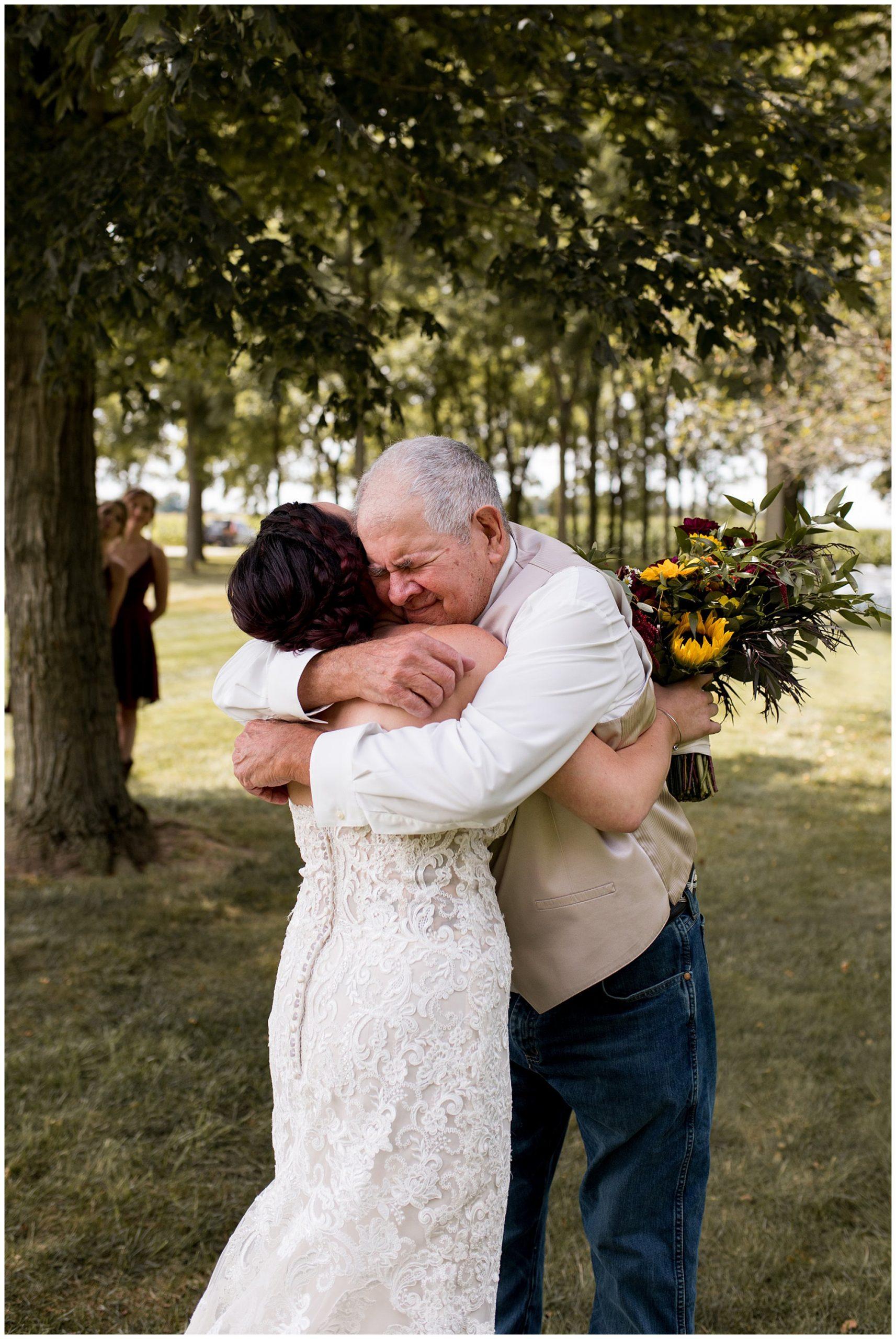 bride's grandpa hugs bride after first look at Kokomo's Legacy Barn
