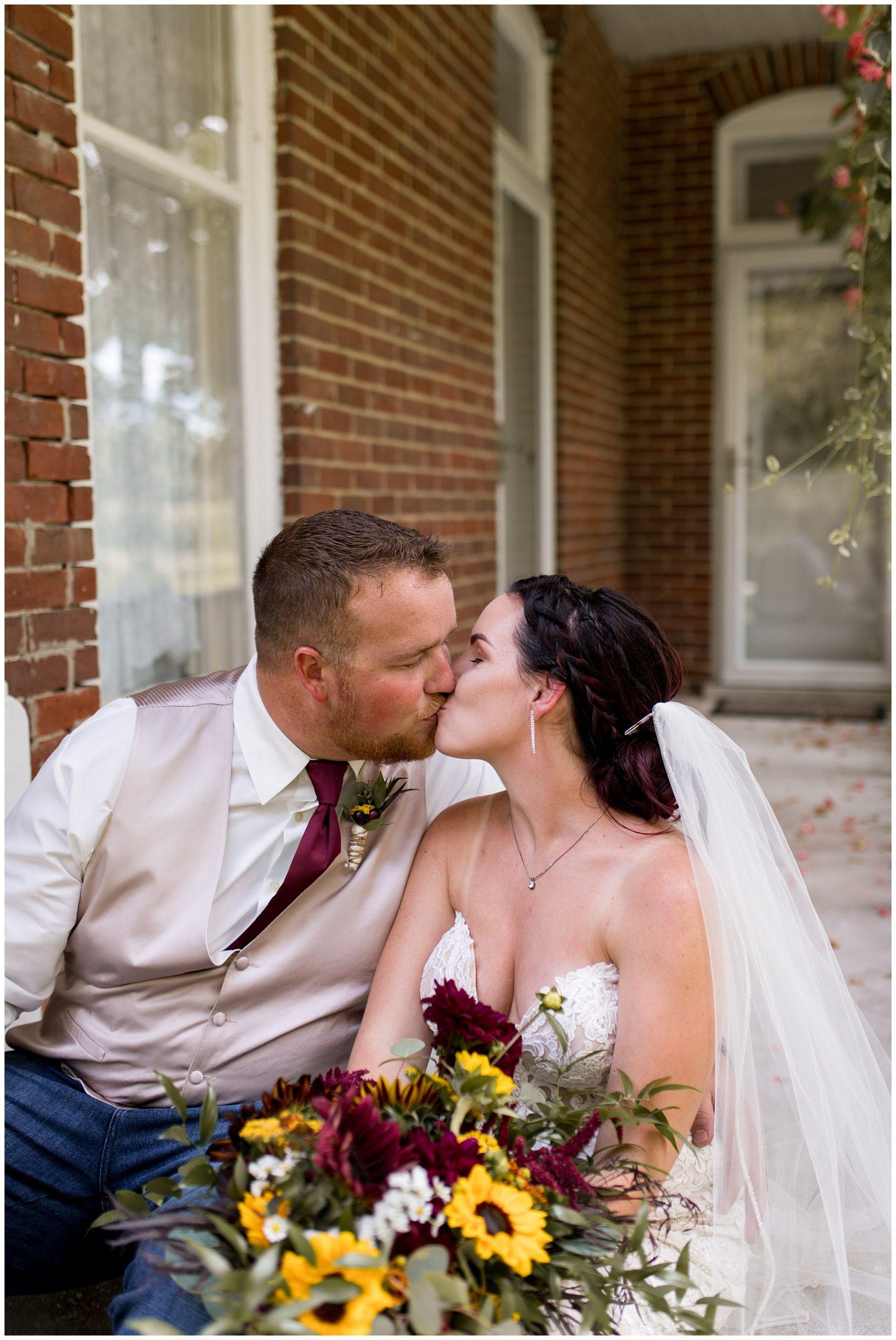 bride and groom kiss on porch at Legacy Barn in Kokomo