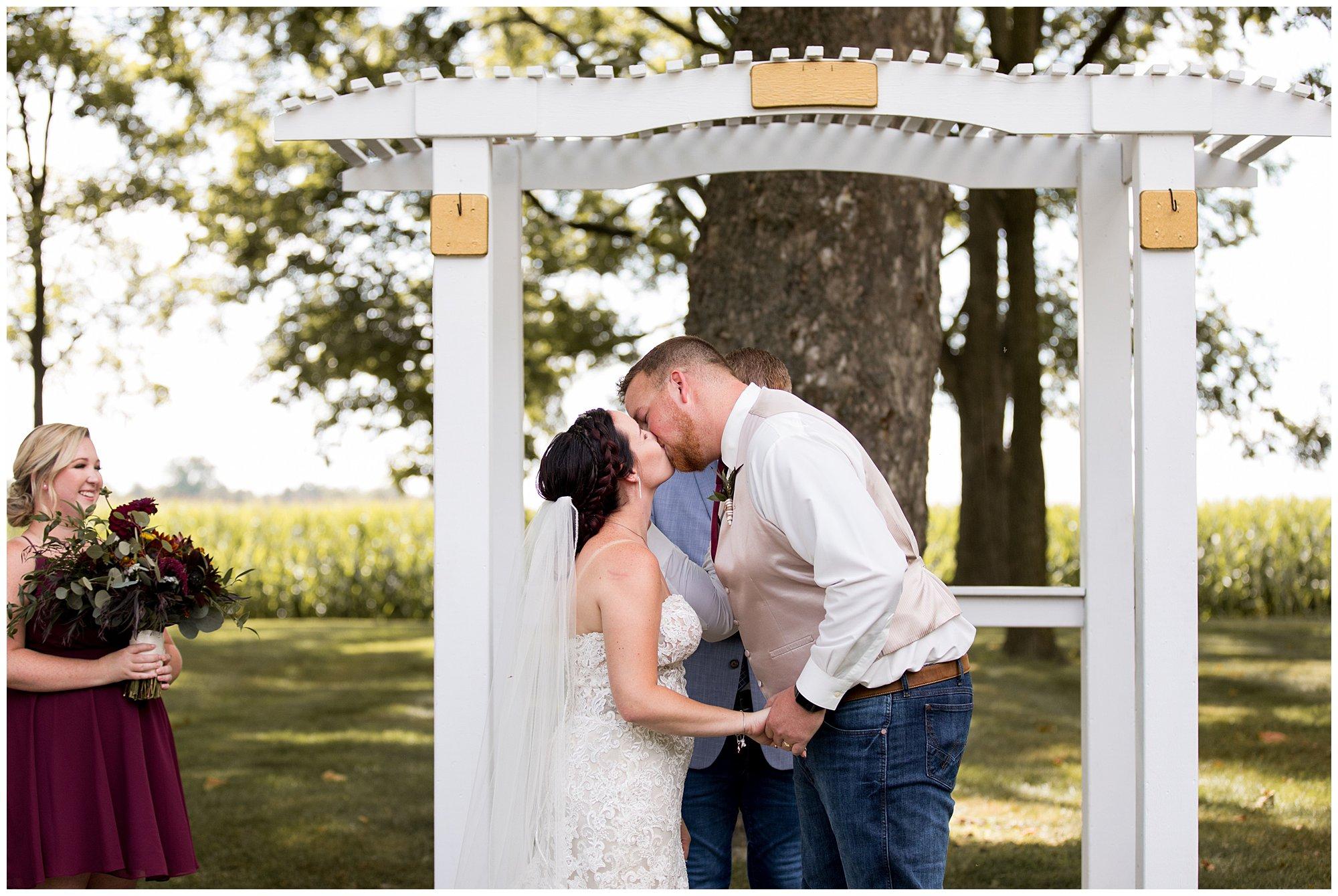 bride and groom first kiss at walnut grove in Kokomo