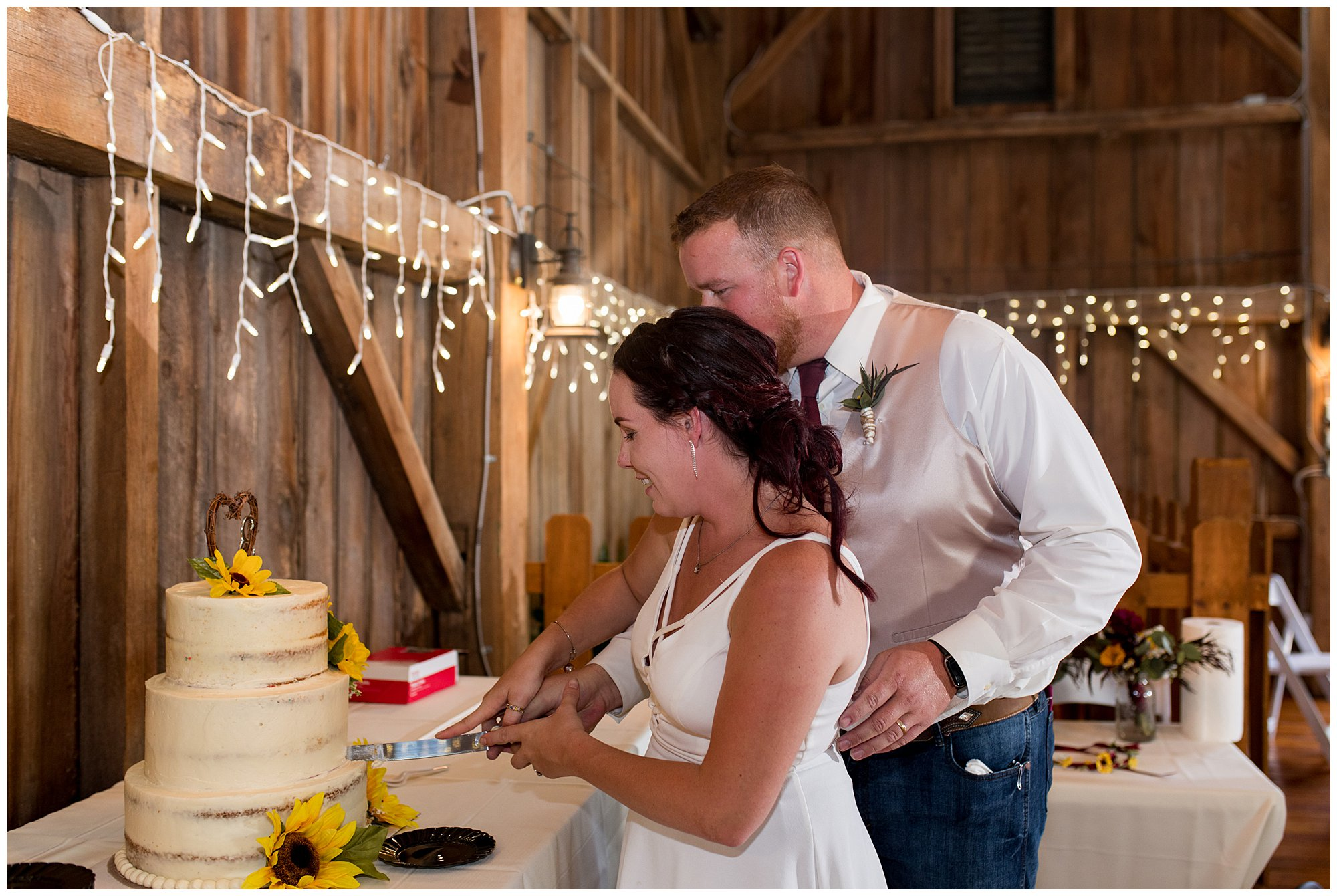 bride and groom cut cake during Legacy Barn reception